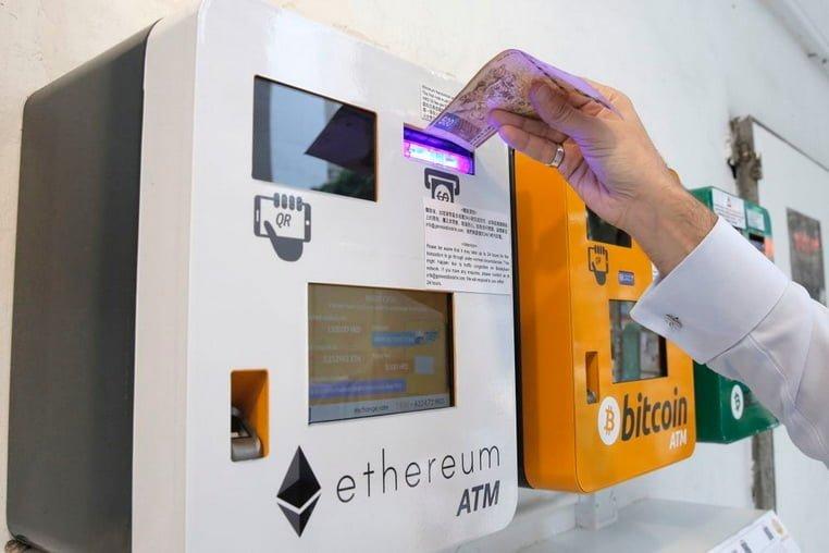 Мужчина пользуется банкоматом Ethereum в Гонконге