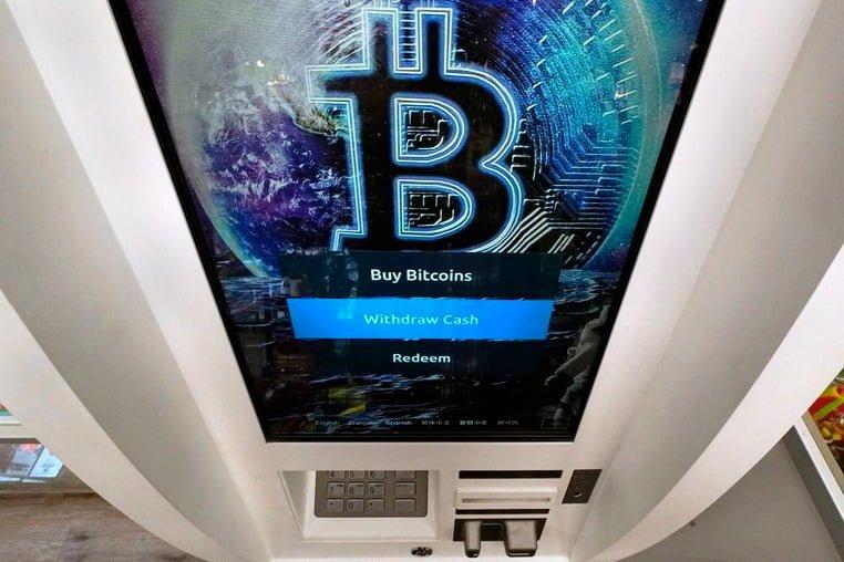 Логотип Биткойн появляется на экране банкомата с криптовалютой в магазине Smokers Choice