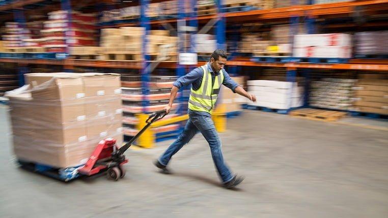 Работник на складе перевозит товар